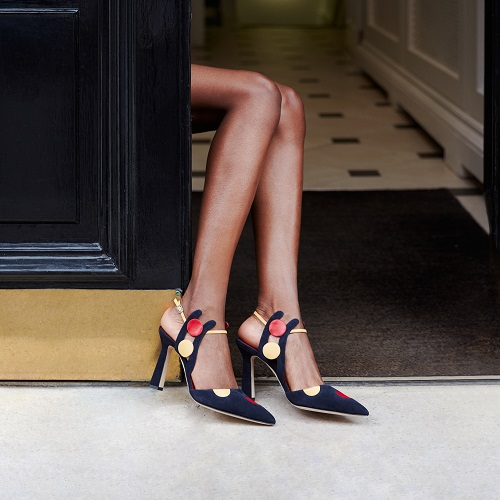 A pair of legs in a doorway with navy suede shoes