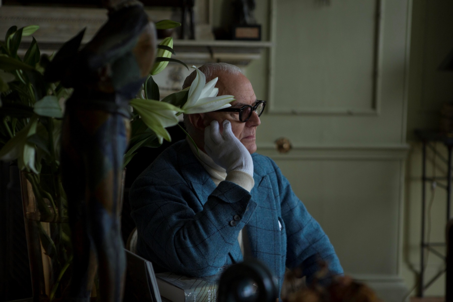 Manolo Blahnik in his study with a beautiful vase of lilies