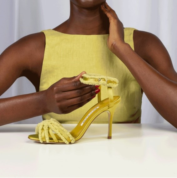 A woman in a lime green top holding a lime green satin shoe
