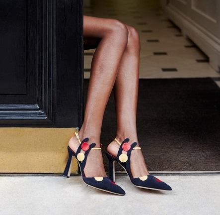 A pair of legs in a doorway wearing navy and yellow suede shoes