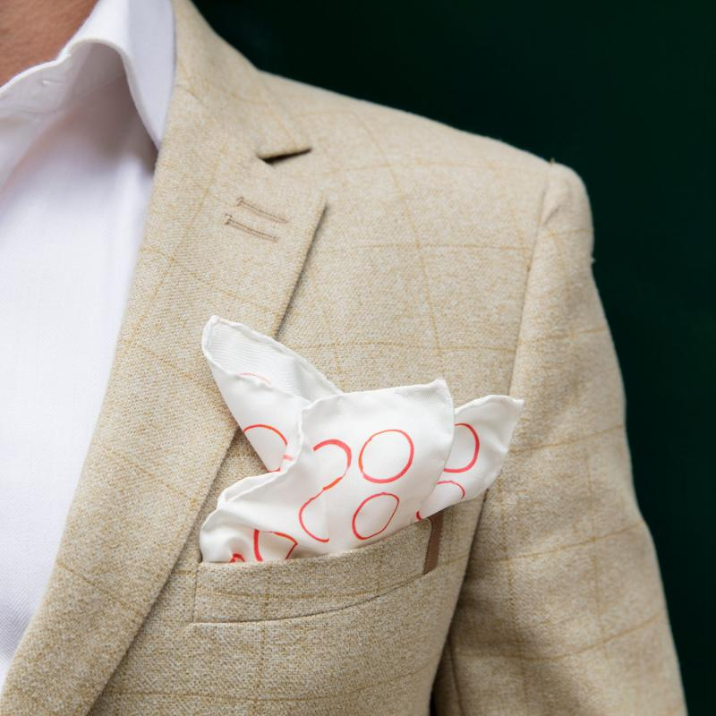 The red and white 'circles' pocket square being worn in the top breast pocket of a man's suit.
