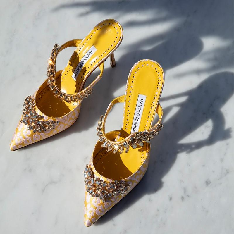 Editorial image of the yellow jacquard mule, Lurum, against a marble background.