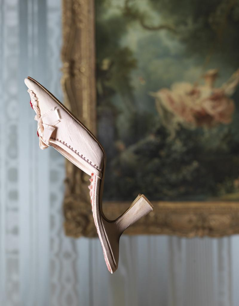 A manolo blahnik shoe suspended in front of a painting