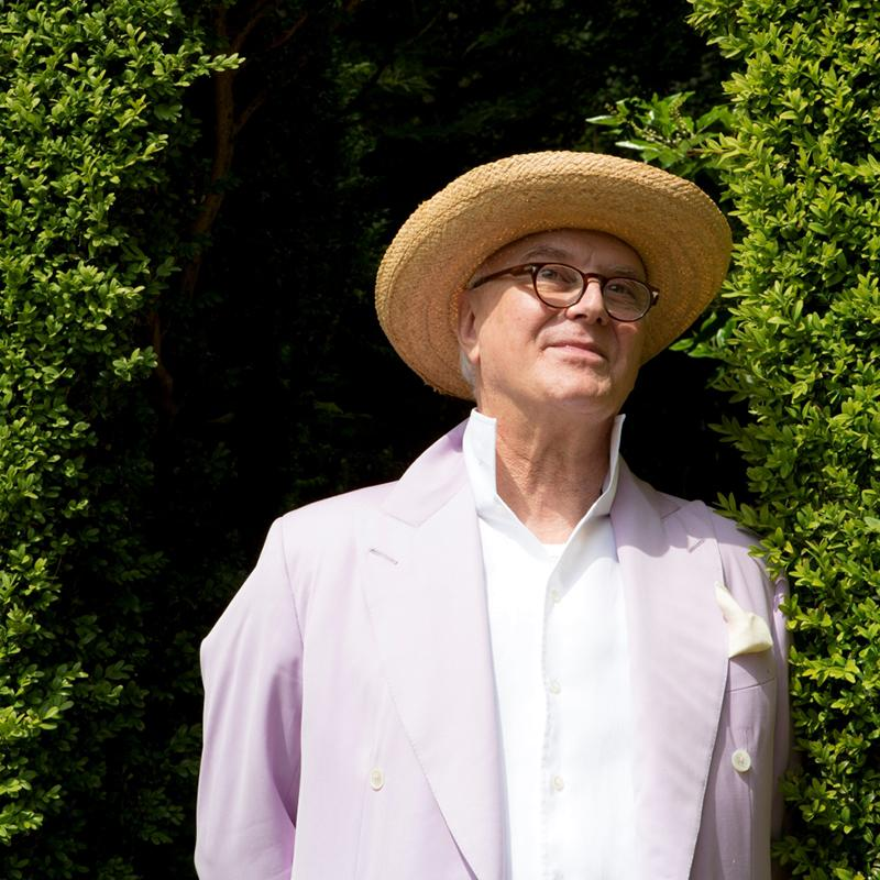 Manolo Blahnik in a garden staring fondly at the nature surrounding him