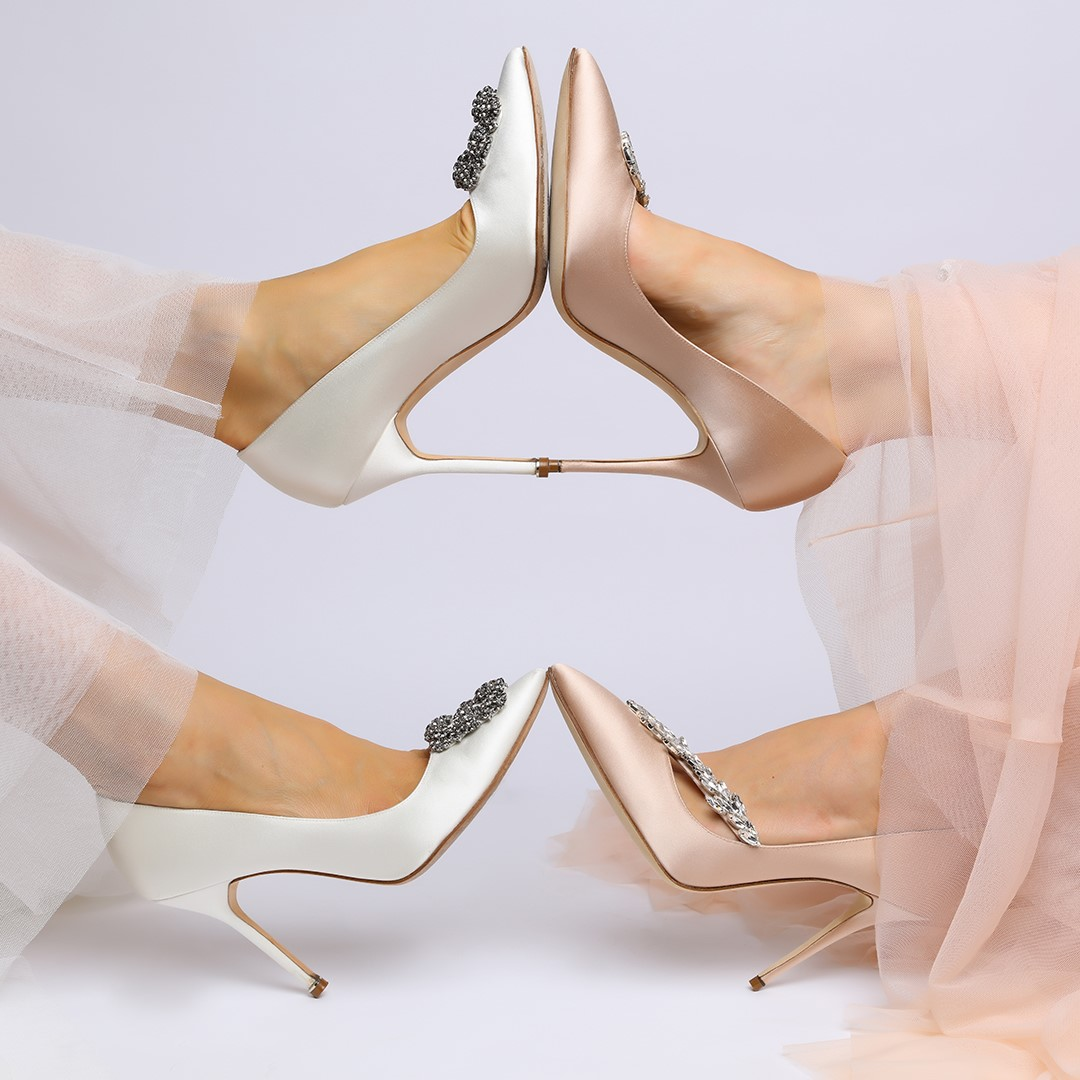 A close up of white satin shoes and champagne satin shoes