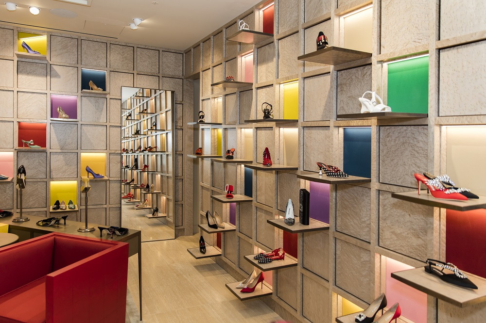 A corner view, inside the Selfridges store. The walls are in a grid with shoes positioned in each square of the grid.