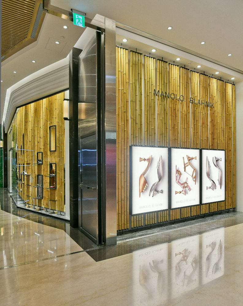 An external view of the Breeze NanShan store in Taipei. There are vertical bamboo canes in the windows.