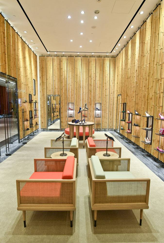 An internal view of the Breeze NanShan store. There are four arm chairs, in pairs back to back and shoes on the walls.