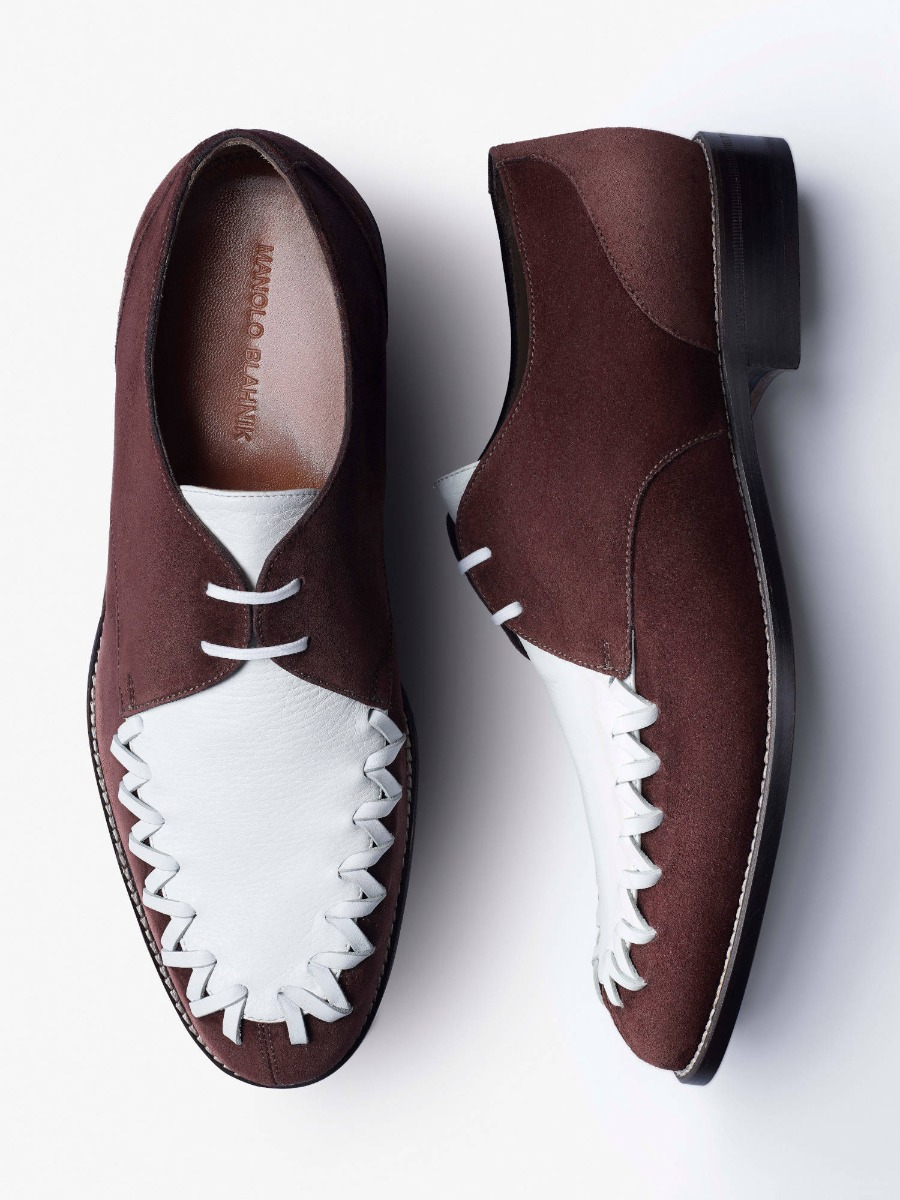 A pair of brown suede and white men's lace ups on a white background. There is oversized cross stitch detail on the shoe.
