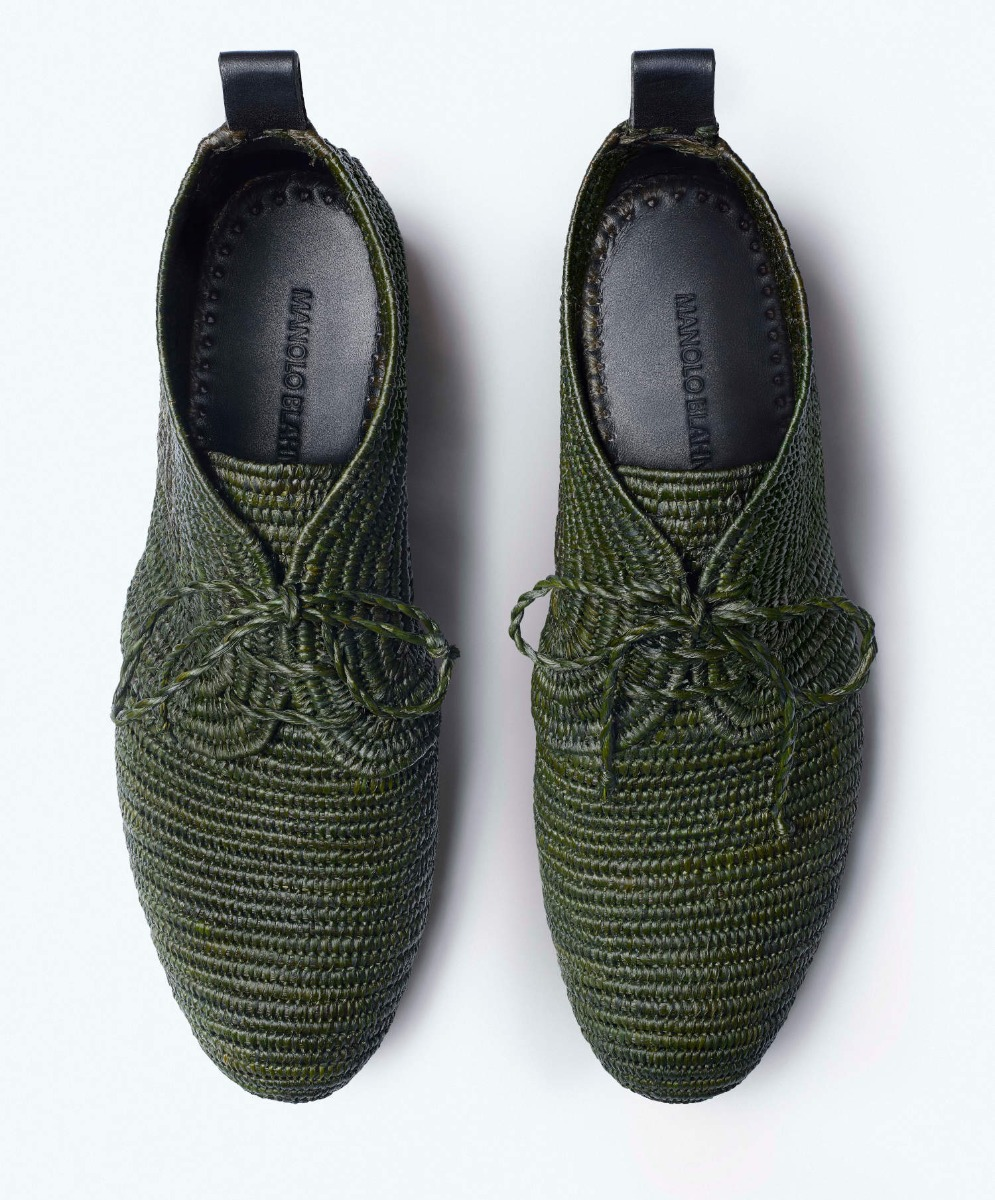 A pair of men's green angle boots made from hand woven raffia. The shoes are in parallel and are on a white background.