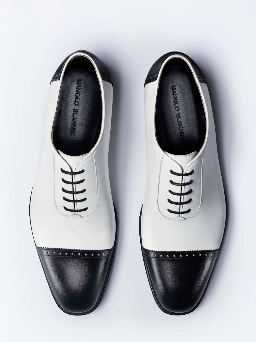 A pair of black and white men's lace up shoes.