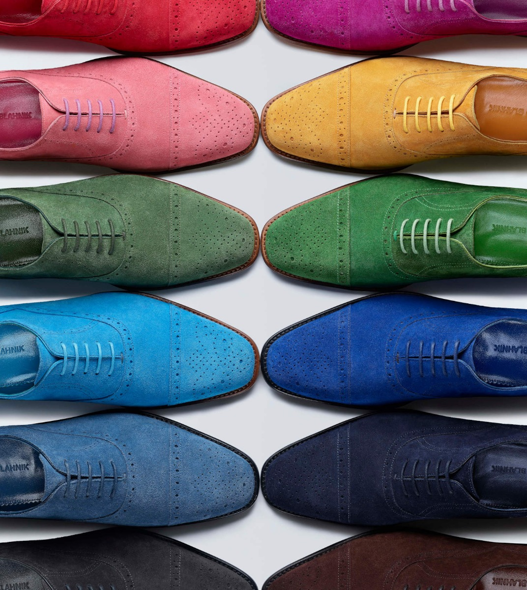 Two rows of single men's lace up oxfords. The shoes are made of suede and are positioned in a colour spectrum.