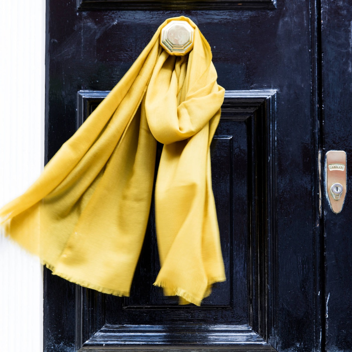 The 'Iona' dark yellow superfine cashmere scarf wrapped around an exterior gold door handle.
