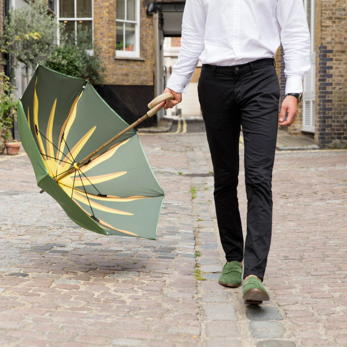 A man on a cobbled street wearing green loafers. He is holding a green umbrella with a sunburst print inside the umbrella.