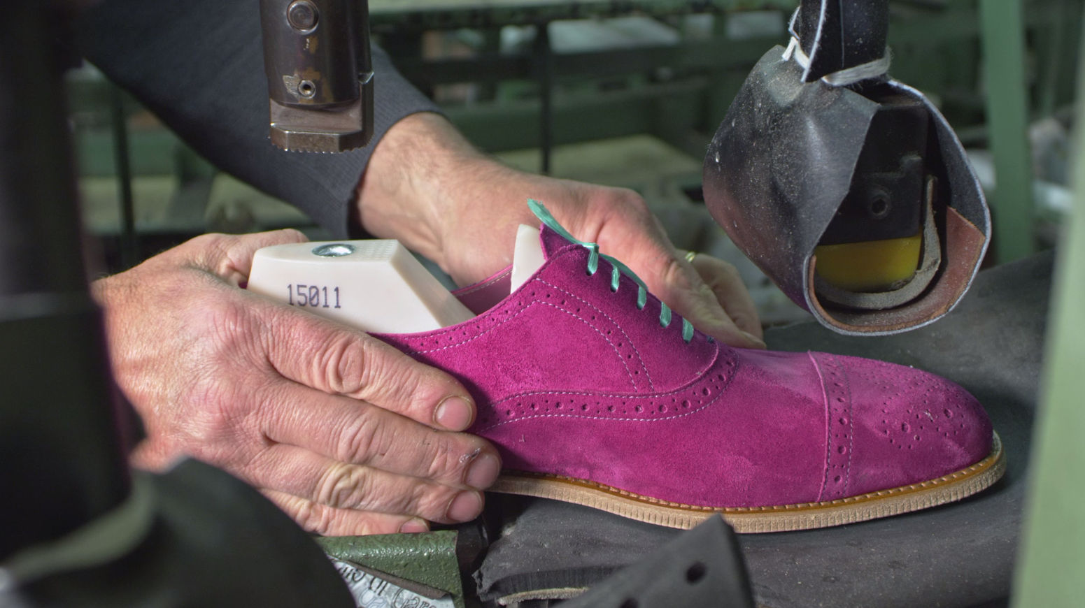 The pink Witney men's Oxford shoe being made in the factory. The shoe is being held at the heel by a craftsman.