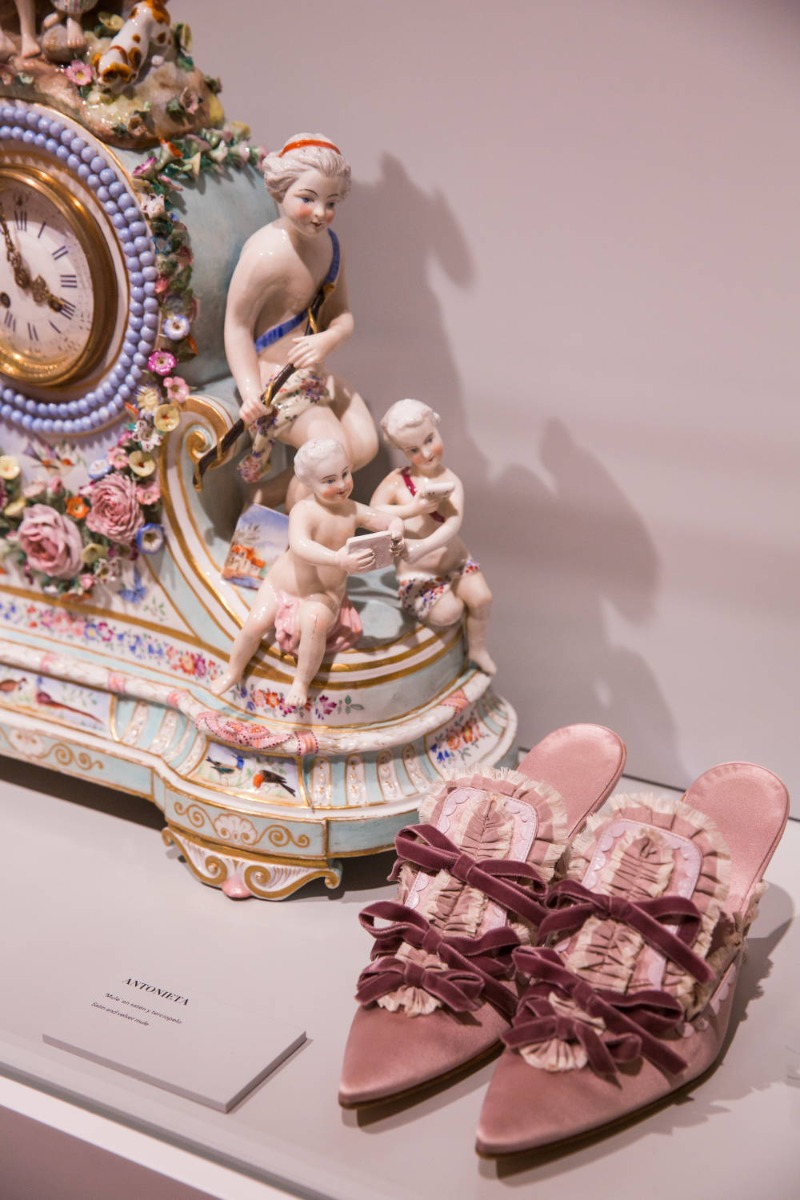 A pair of pink shoes designed for Sofia Coppola's film Marie Antoinette, next to an ornate pink clock.