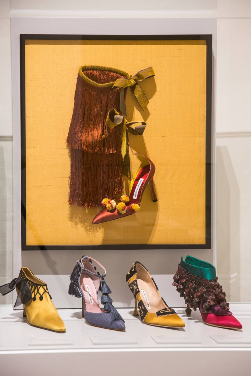 The Art of Shoes Exhibtion. A knee high shoe with brown tassels (which go from the knee to foot) is attached to the wall.