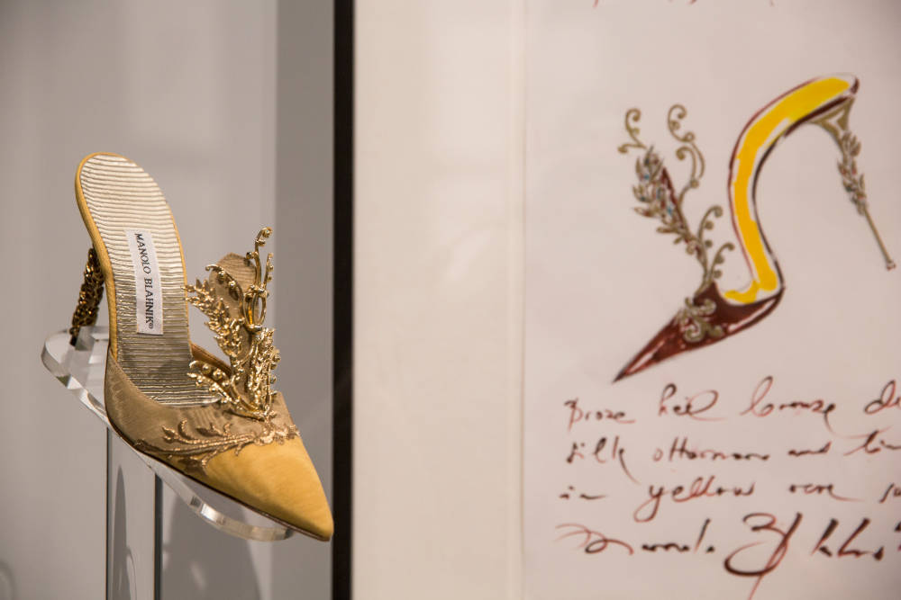 A yellow high heeled mule on show at the exhibition. Behind the shoe, on the wall is the original sketch.