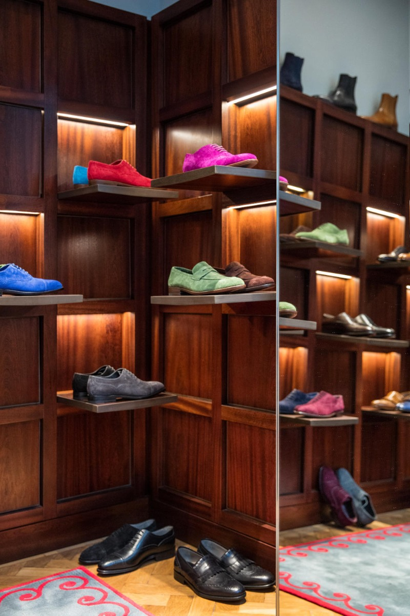The first floor of the Men's store. A corner view, there are small shelves on the walls with a pair of shoes on each shelf.