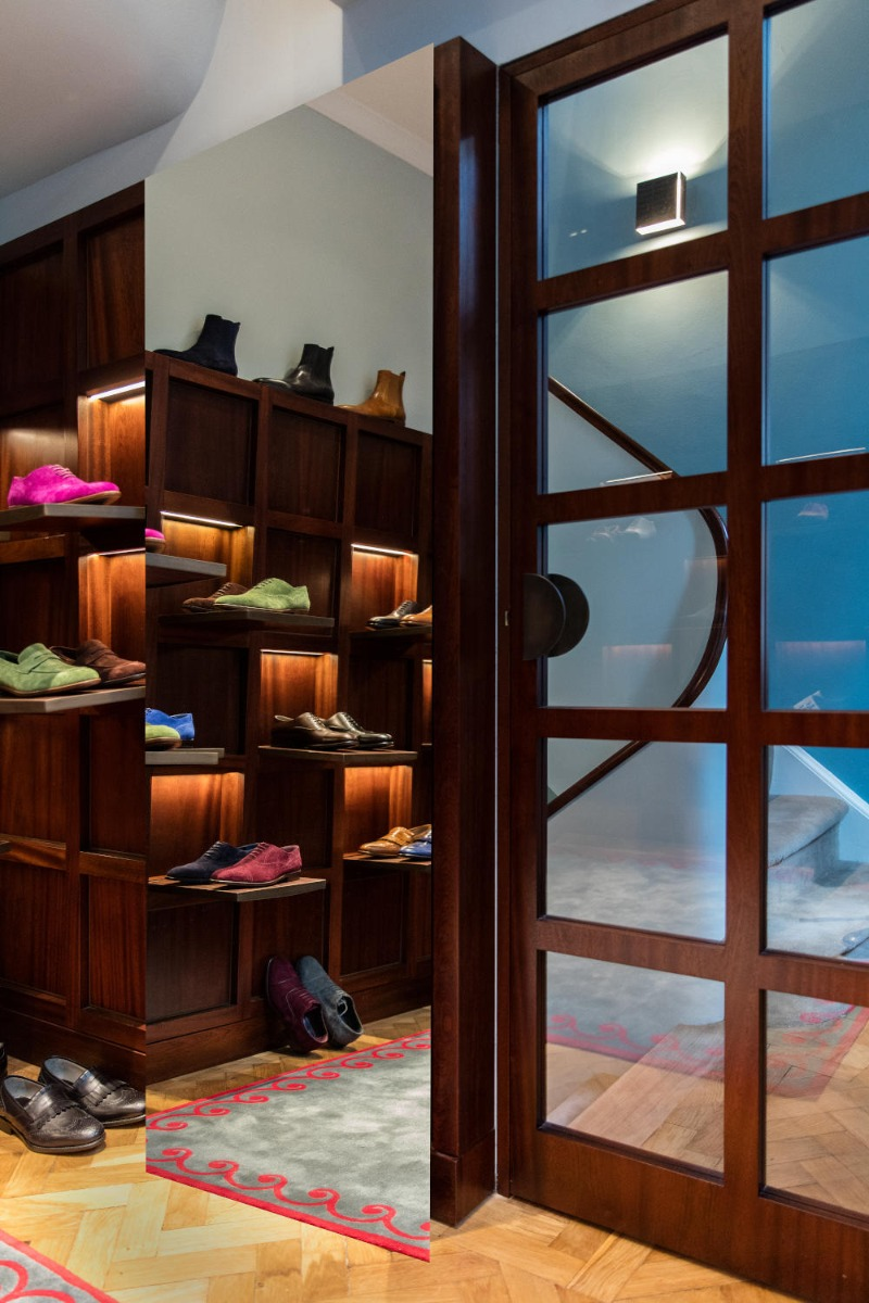 Inside the Men's store in London. In the corner there are colourful mens shoes on shelves.