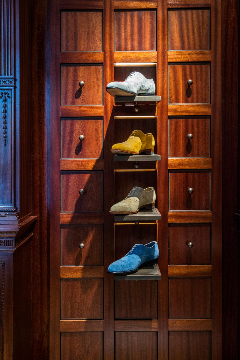 Four colourful mens shoes in the mens shop. The shoes are vertically aligned one under the other.