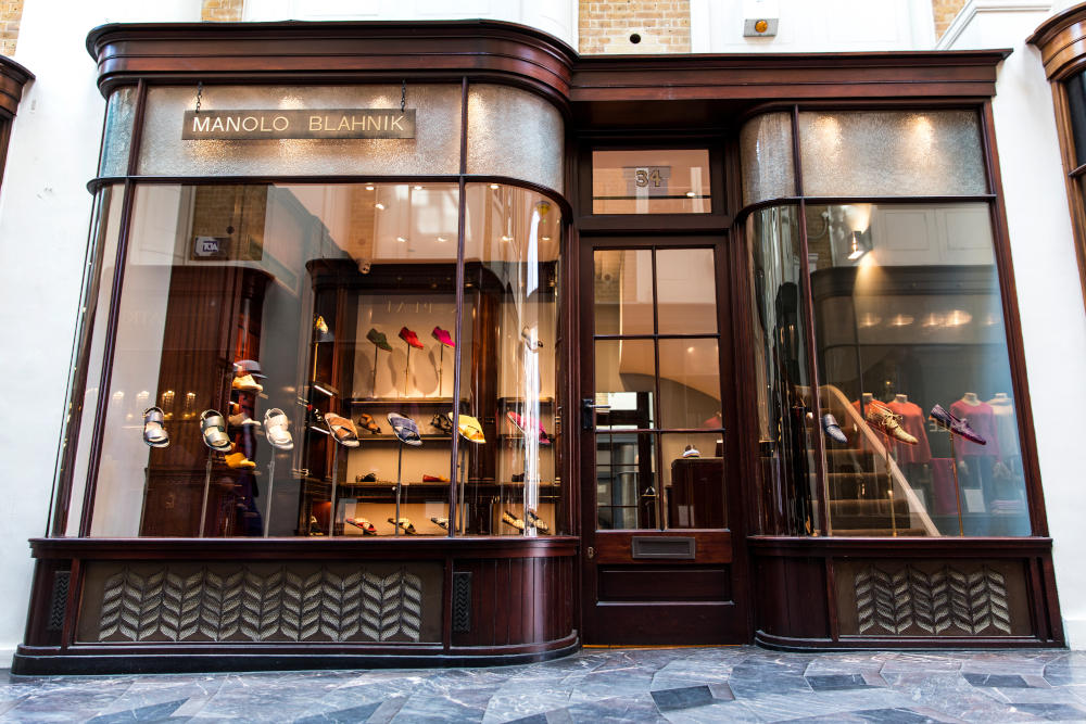 The Manolo Blahnik Men's store. A double fronted store with mahogany wood frames around the windows and door.