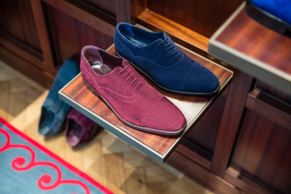 One burgundy and one blue mens suede shoe, next to each other on a square shelf. The shelf is made of a dark wood.