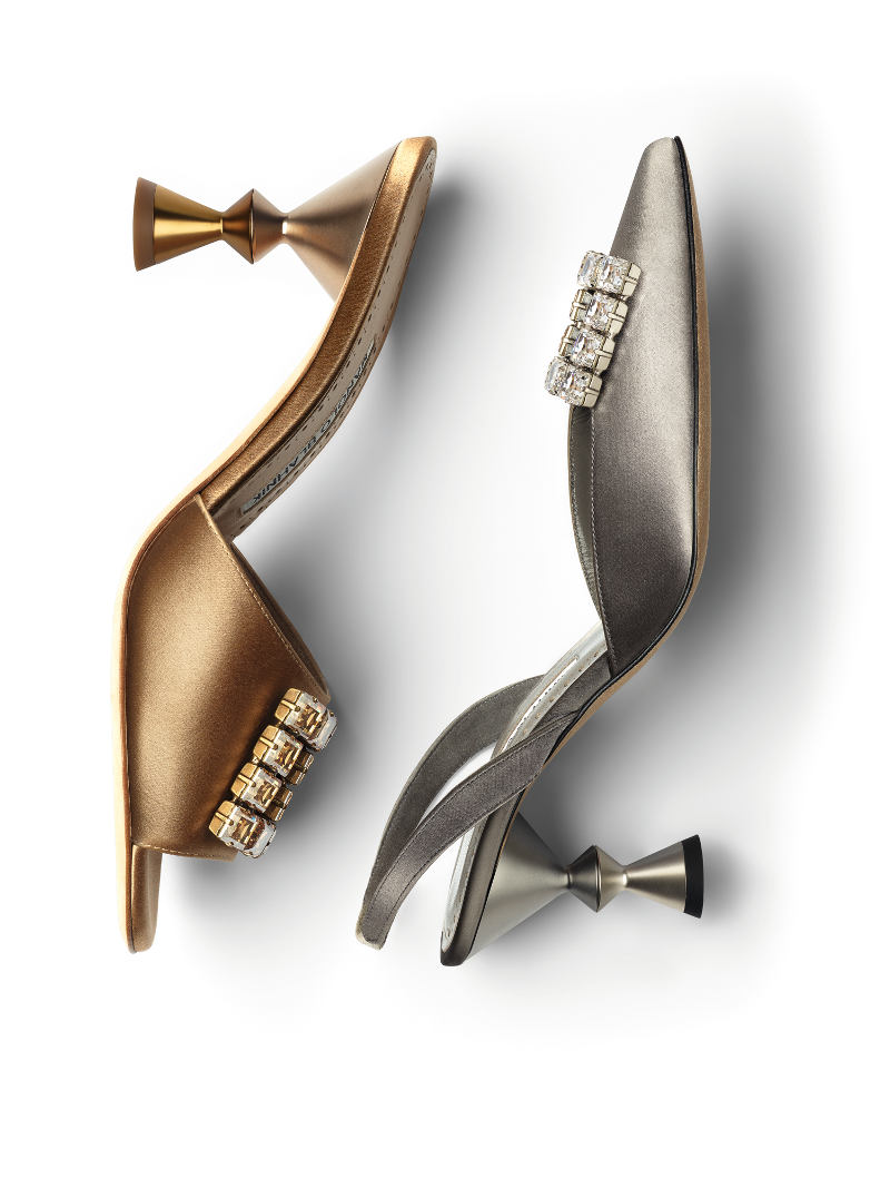 A gold shoe on the left and a silver shoe on the right, both have a sculptural heel. Both shoes have jewelled embellishments