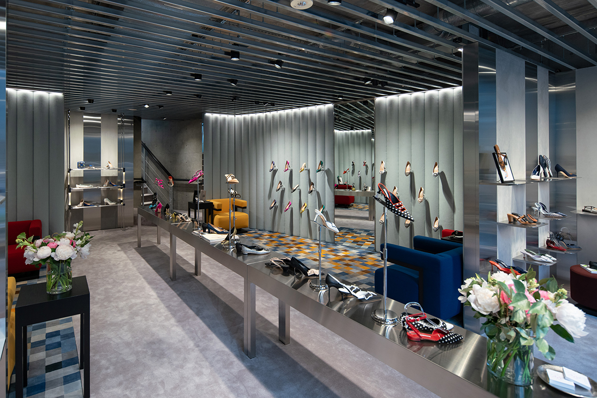 The Omotesando, Tokyo store. A brushed aluminium table with shoes on it runs down the centre of the store.