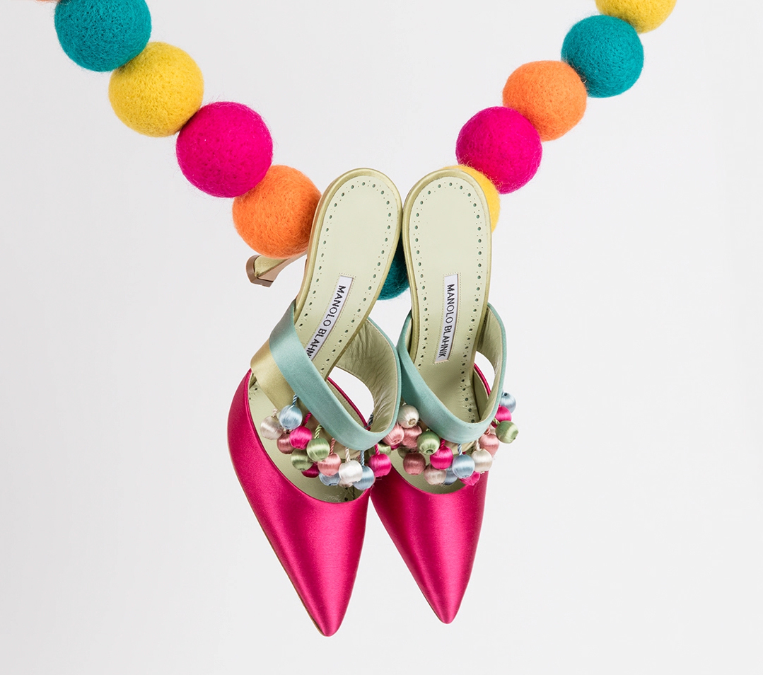A pair of pink heeled mules with pom pom tassels. The mules are hanging from a chain of pom poms.
