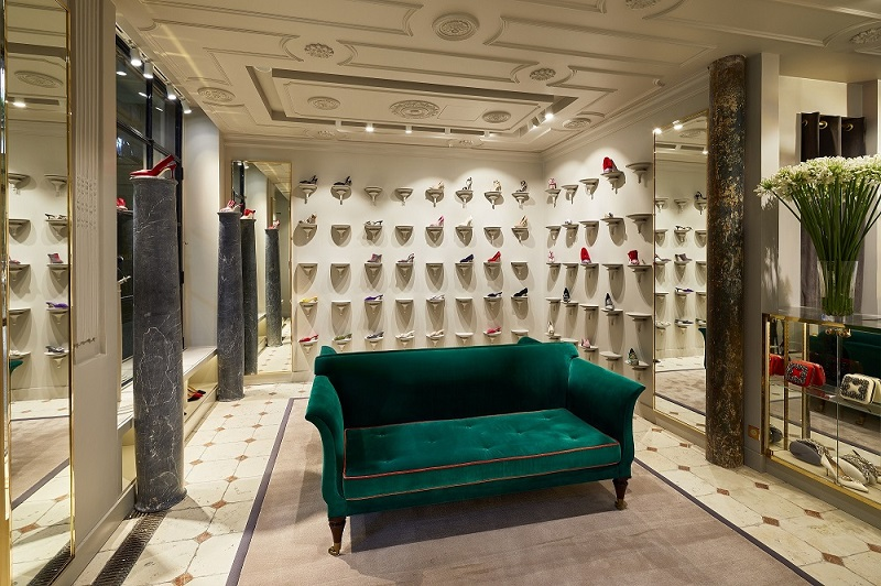 Inside the Paris store. Shoes are positioned on individual shelves. There is a deep green sofa in the middle of the space.