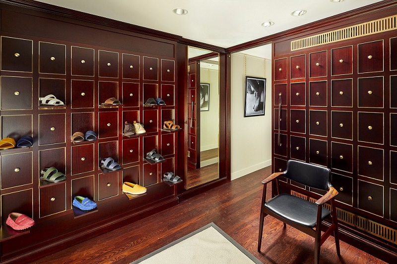 The Men's shoes area of the store. There is mahogany wall panelling, stained oak floorboards and a Hoffman chair.
