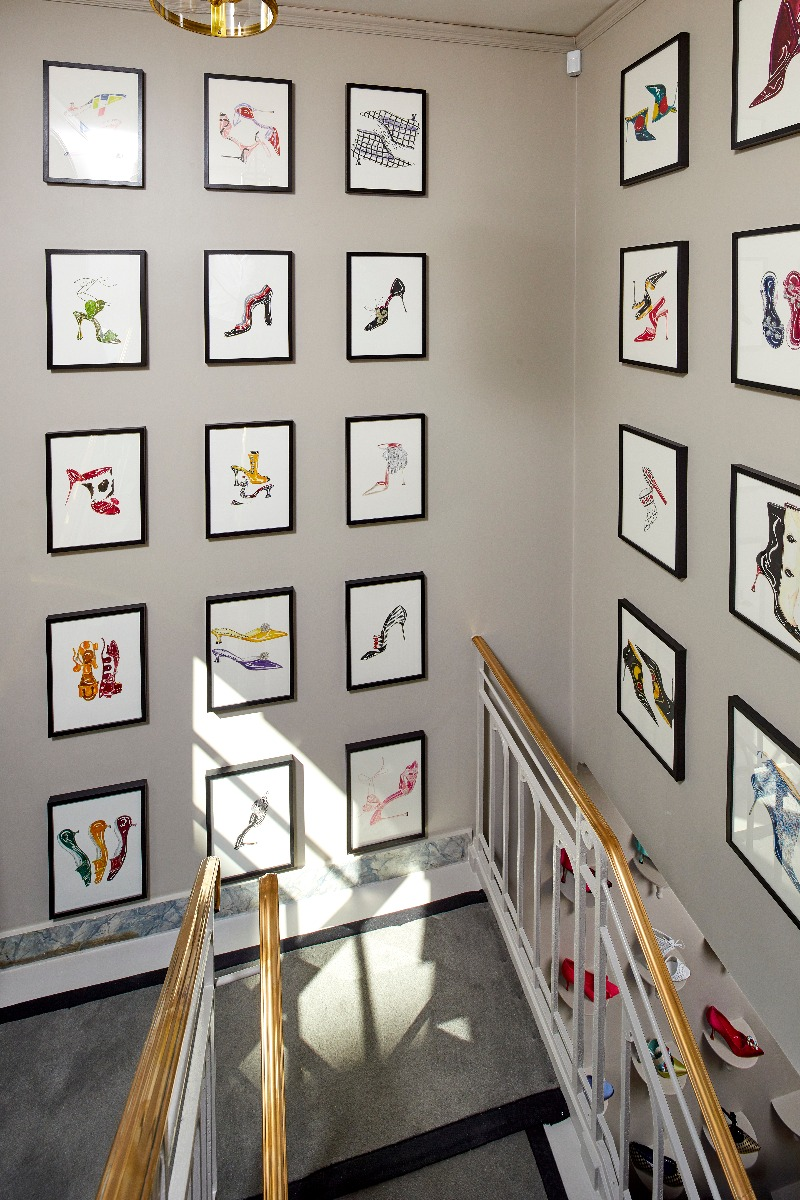 The staircase of the Paris store. The walls feature a gallery of Manolo's sketches.