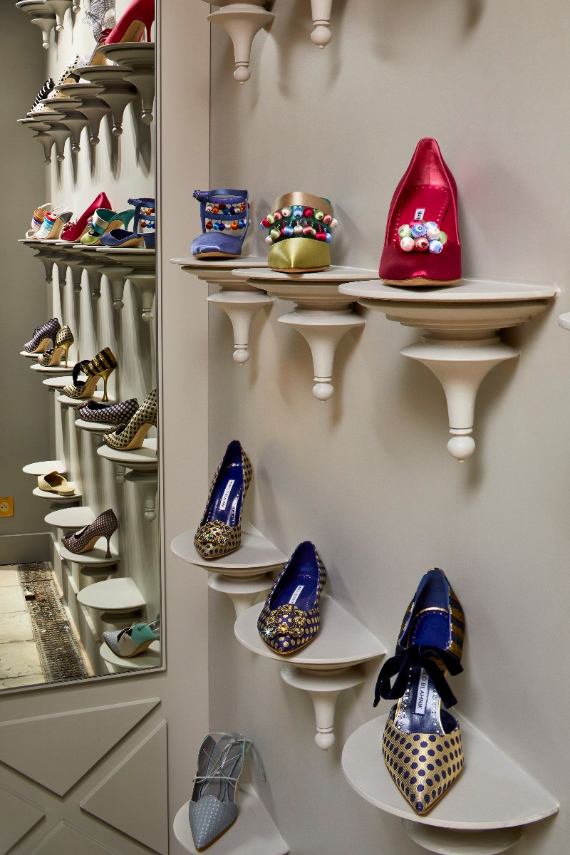 Shoes in on individual conical shelves in the store. The shoes are in profile and also reflected in a mirror to the side.