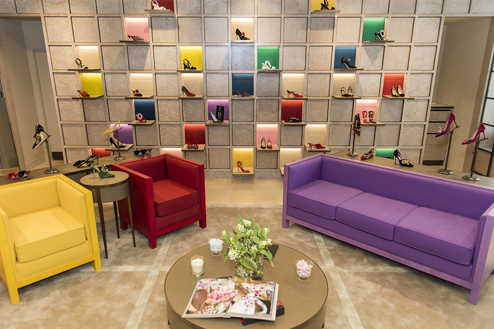 Inside the new store, there are brightly coloured chairs. Along the back there  are square shelves with shoes on.