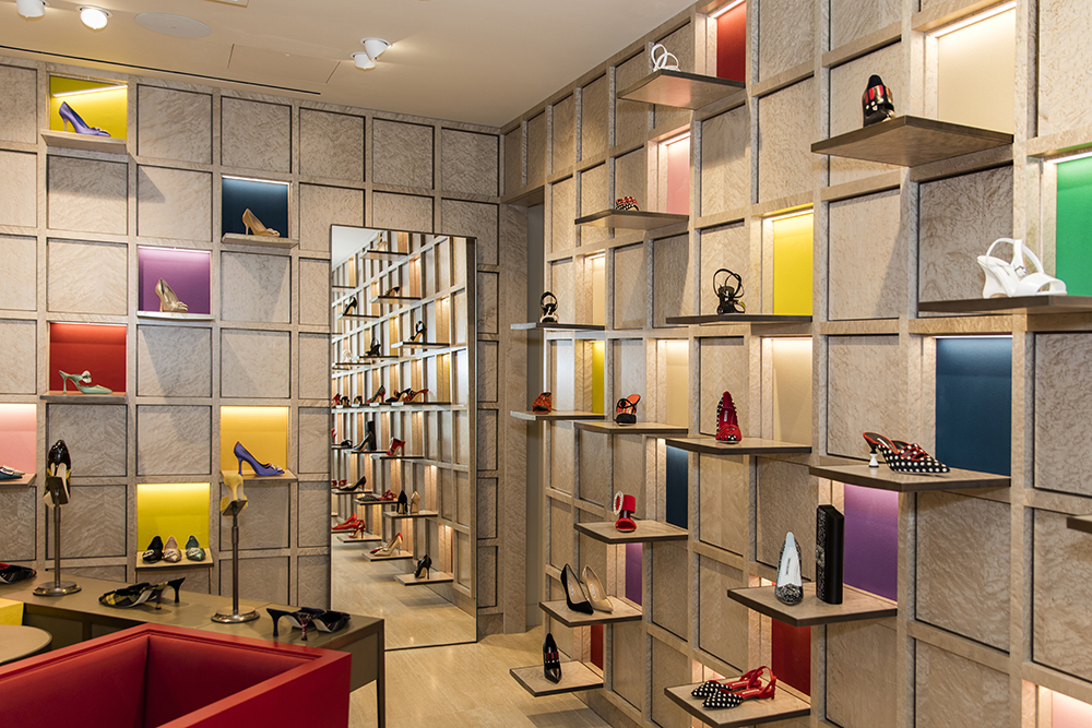 A corner view, inside the store. There are square shelves with shoes on along the walls, and a mirror in the corner.