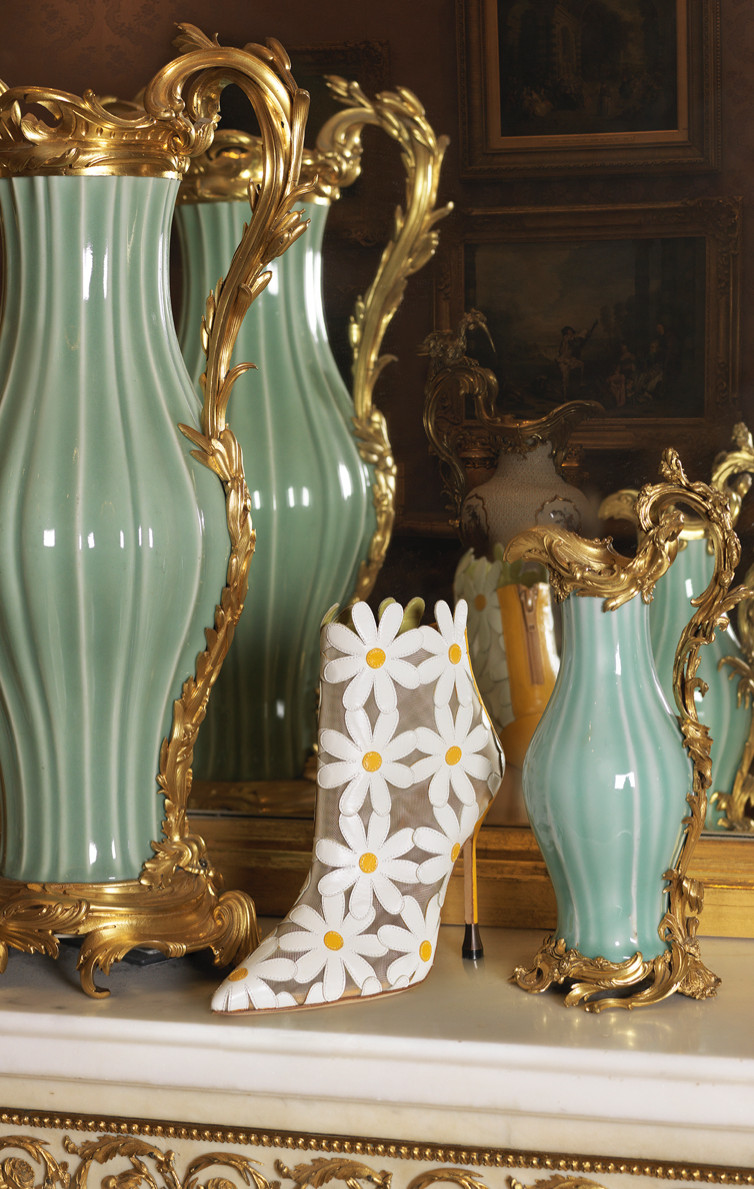 The Margolotta Boot. A boot featuring oversized daisies is positioned in front of a mirror and between two ornate vessels.