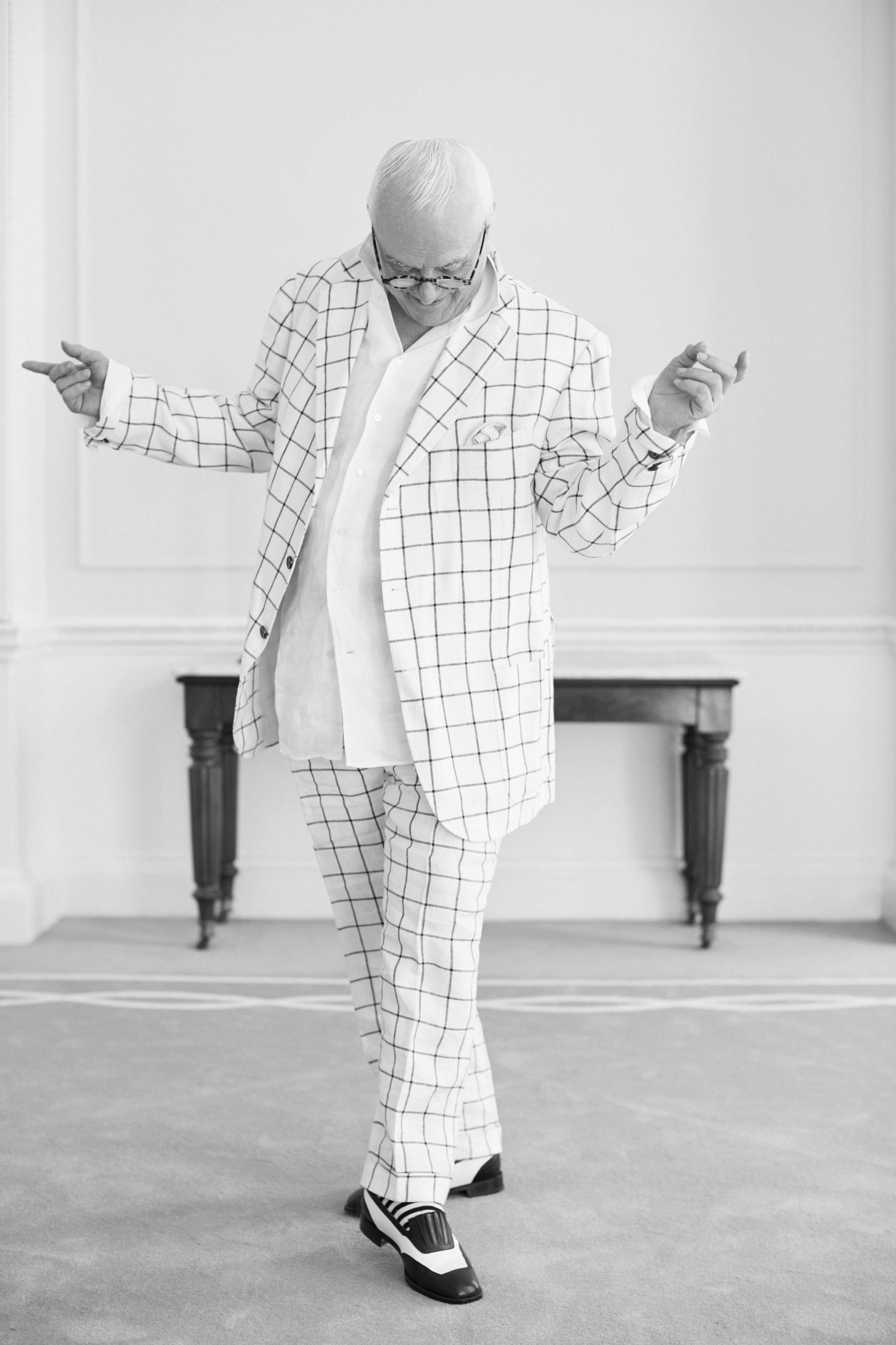 Manolo Blahnik wearing a white suit. He is looking at his feet. His hands are up in a whimsical and fun position.