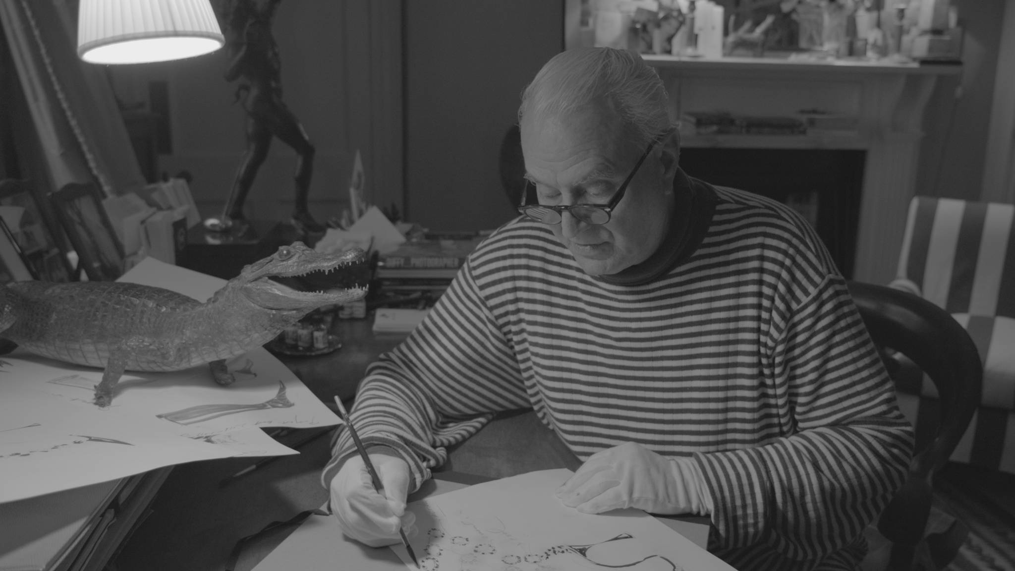 A black and white image of Manolo sketching a shoe. He is wearing a Breton turtle neck and white gloves.