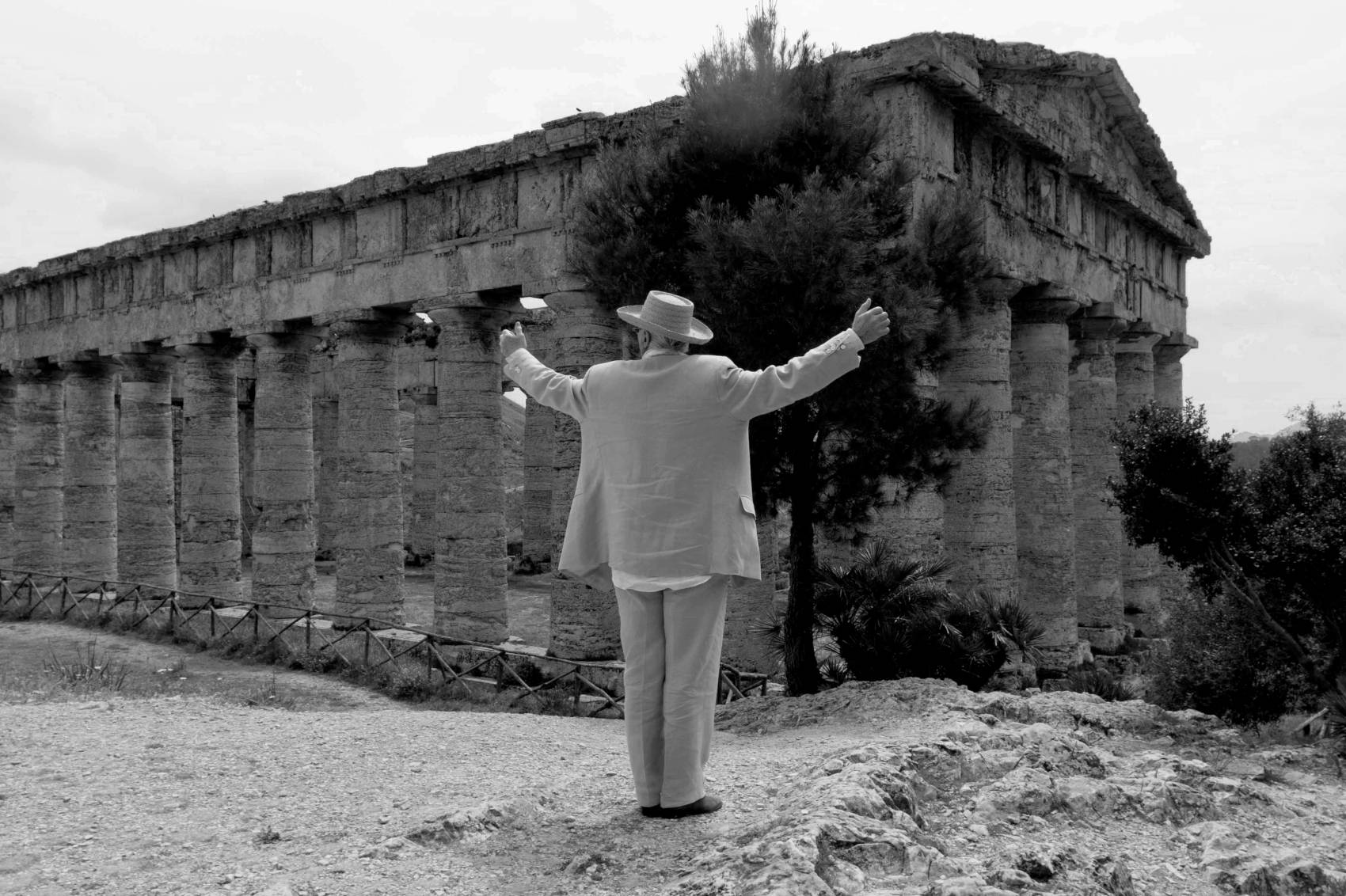 Manolo stood in front of an ancient ruin. He has his back to camera with his arms in the air.