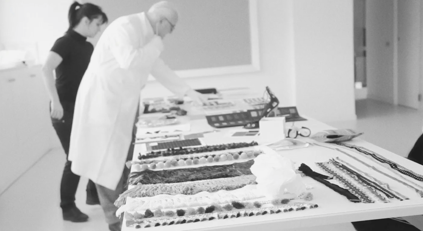 A black and white image of Manolo Blahnik at the factories, he is seen in profile, wearing a white lab coat.