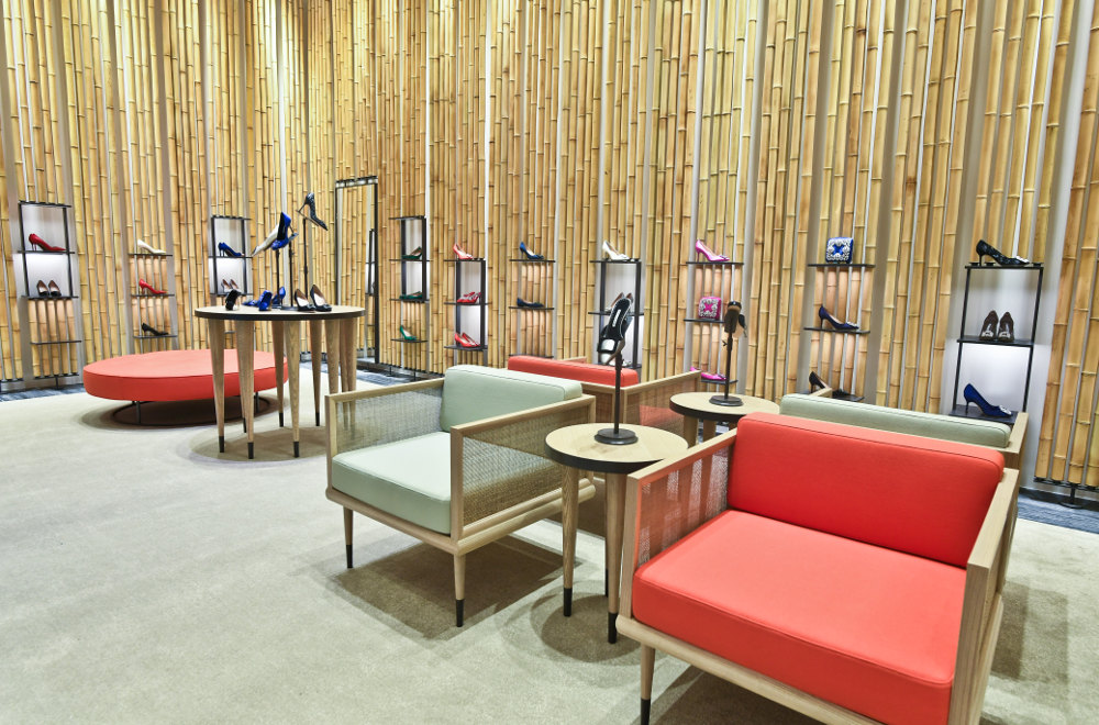 An internal view of the Breeze NanShan store. There are arm chairs. There are shoes on circular tables, and the walls.