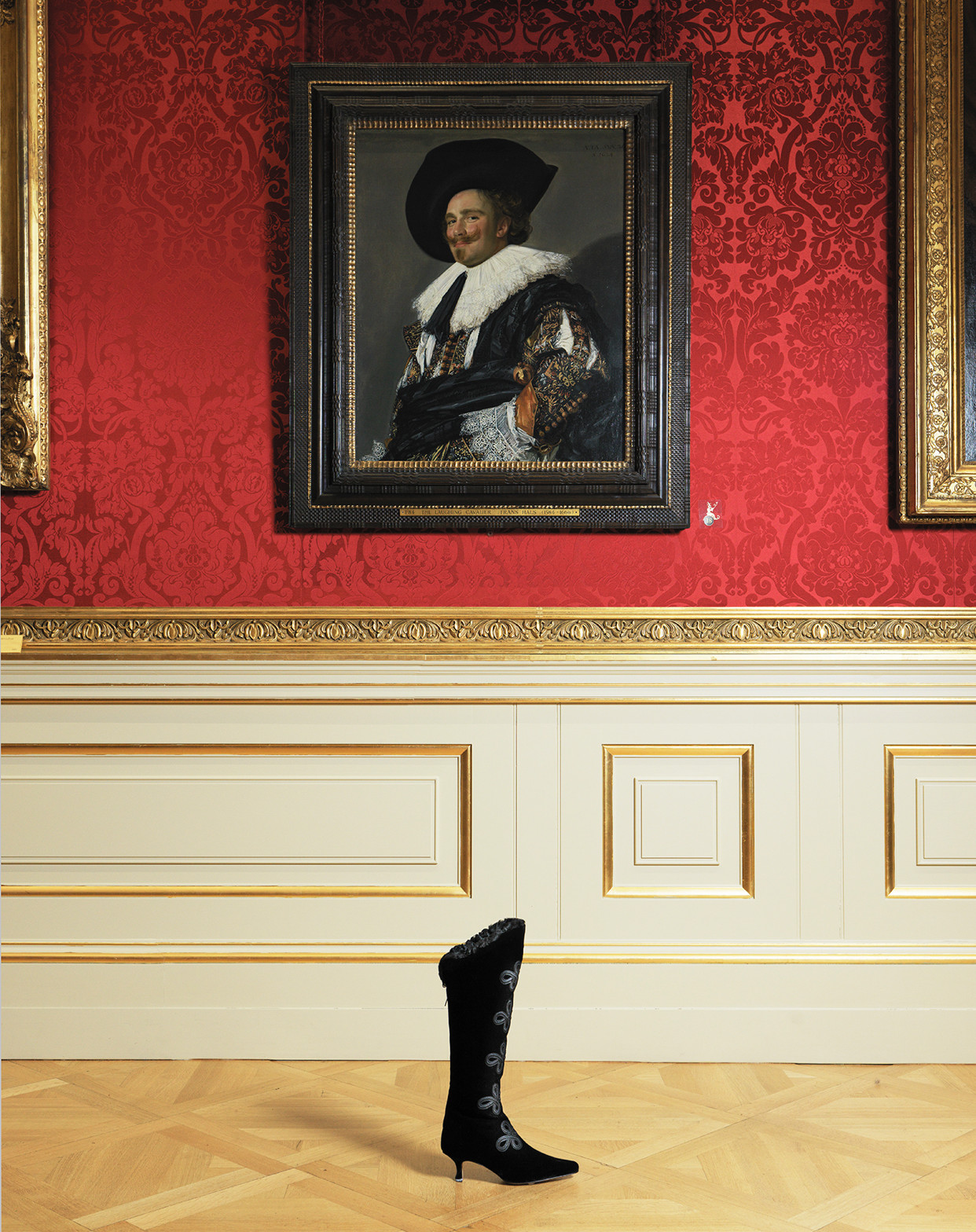 The Asha boot. A black knee high boot with ribbons, is positioned in front of The Laughing Cavalier painting by Frans Hals.