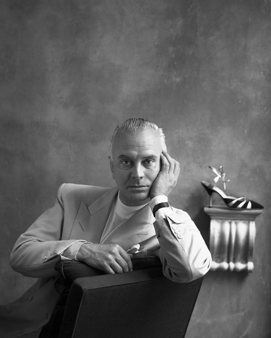 A black and white portrait of Manolo Blahnik. He is in the Old Church Street store, sitting on a chair.