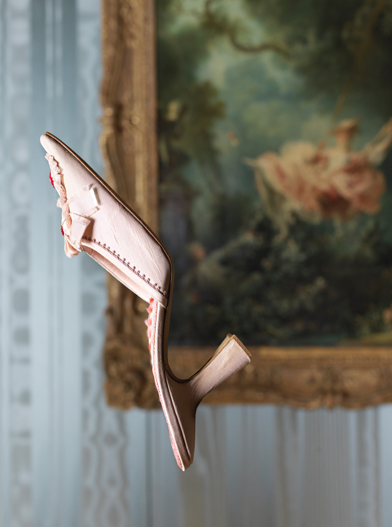 The Versailles shoe. A pink mule is suspended in front of Fragonard's painting, The Swing.